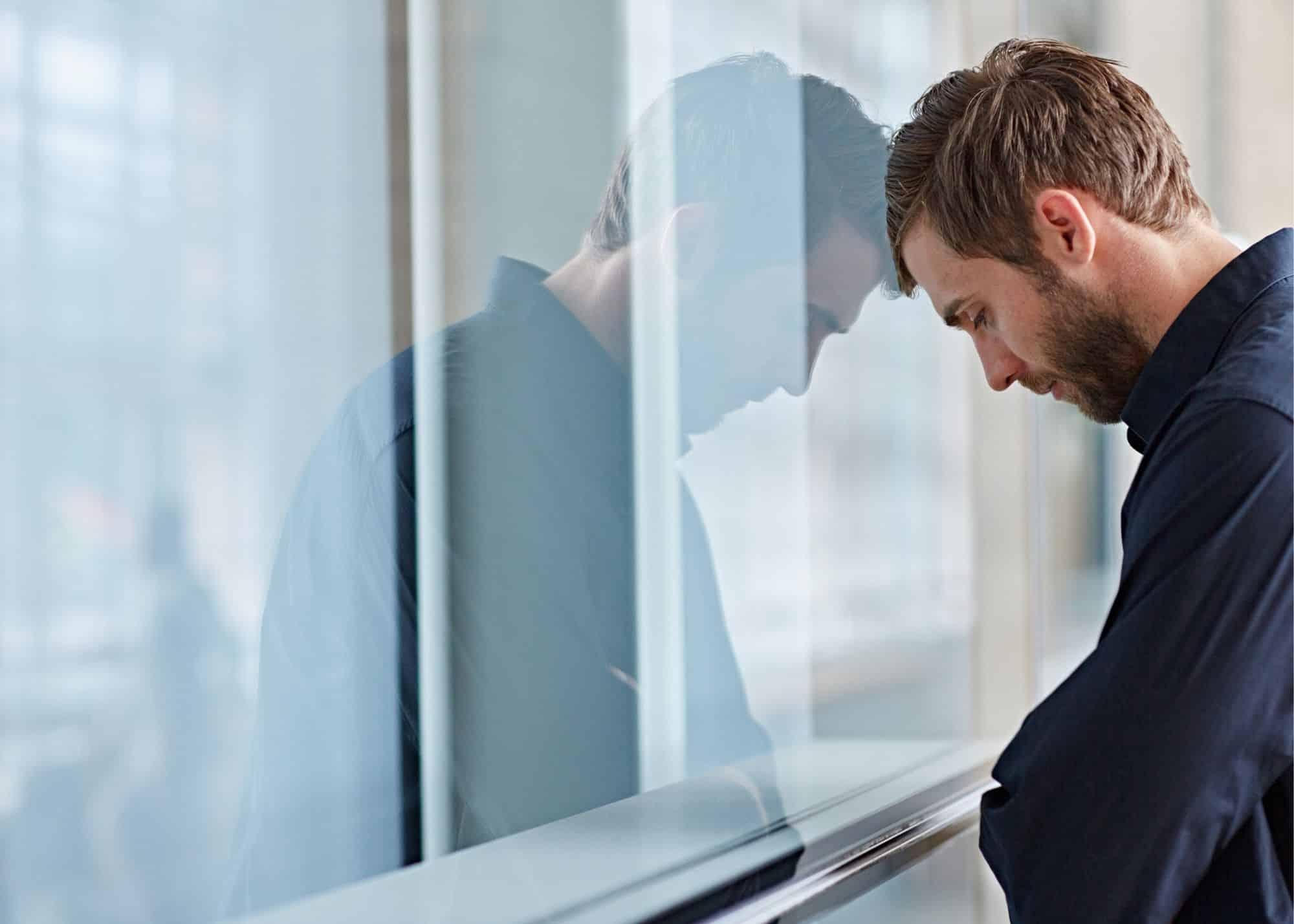Man leans head against wall in desprair